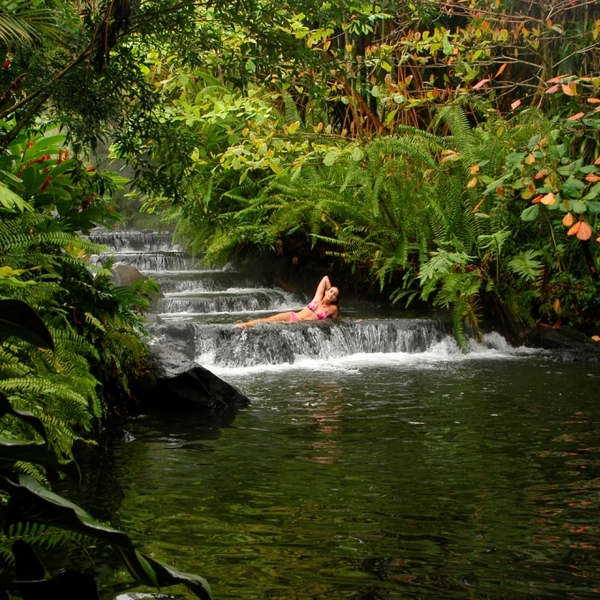 Une jeune femme allongée dans une cascade entourée de végétation