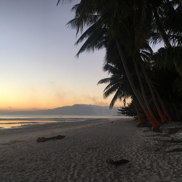 Das Bild zeigt einen Sonnenuntergang am Strand.