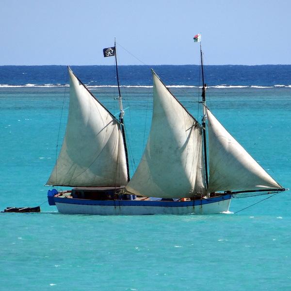 Goélette navigant à la voile dans un lagon
