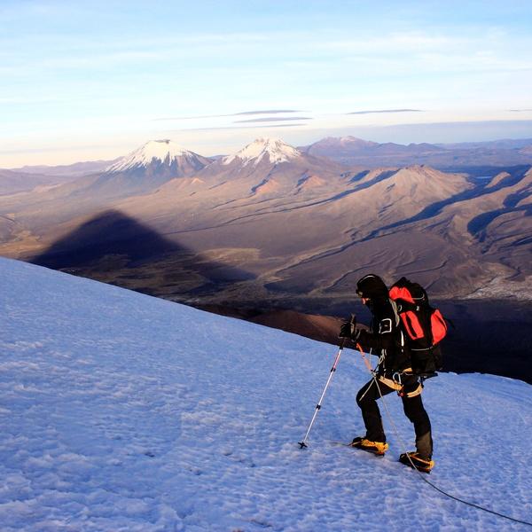 Alpiniste sur une pente enneigée avec des volcans enneigés à l'horizon