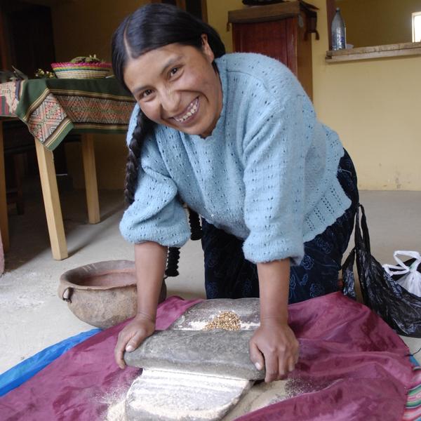 Indienne en train de piler des graines avec des pierres