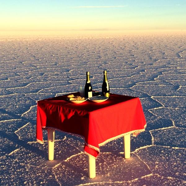 Table dressée en plein désert avec nappe rouge et bouteilles de champagne