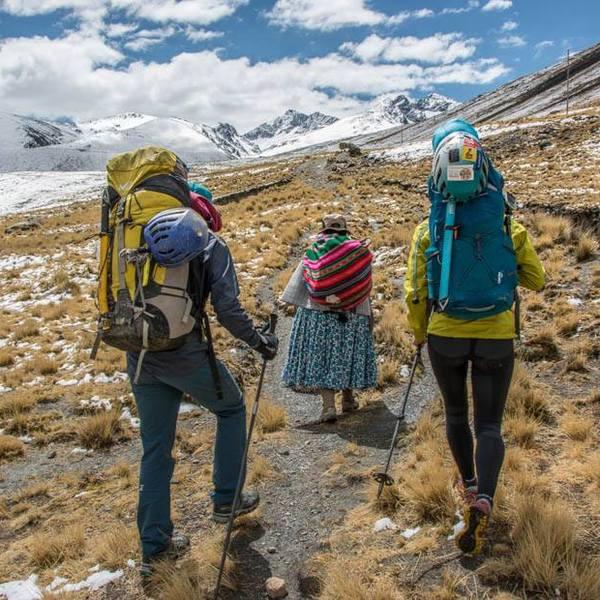 Deux randonneurs marchant derrière une femme en costume traditionnel sur un chemin de montagne