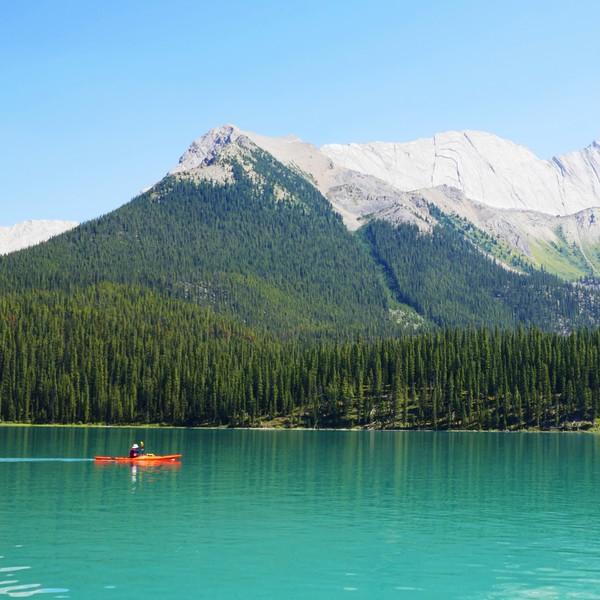 Canoë navigant sur un lac turquoise entouré de forêts et montagnes