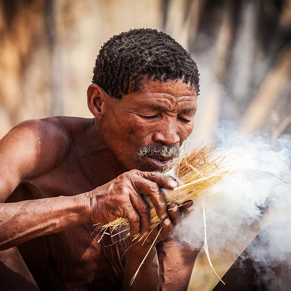 Das Bild zeigt einen San Bushman in den Erongobergen beim entfachen eines Feuers.