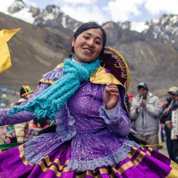 Femme en robe colorée dansant devant un groupe de musiciens