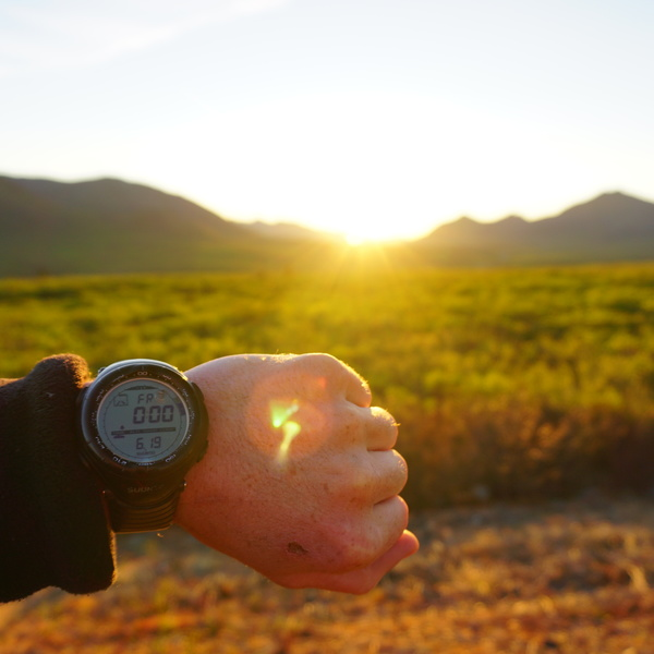 Une montre au poignet d'une personne indiquant minuit avec le soleil brillant derrière