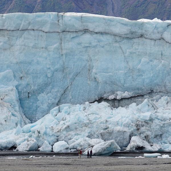 Quelques personnes devant les énormes blocs de glace du glacier Donjek, dans le parc national de Kluane