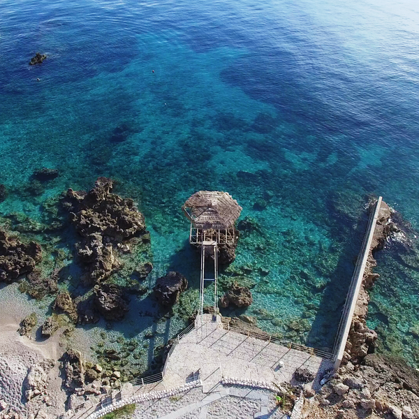 Das Bild zeigt eine Bucht mit türkisfarbenem Wasser und einer kleinen Hütte im Wasser.