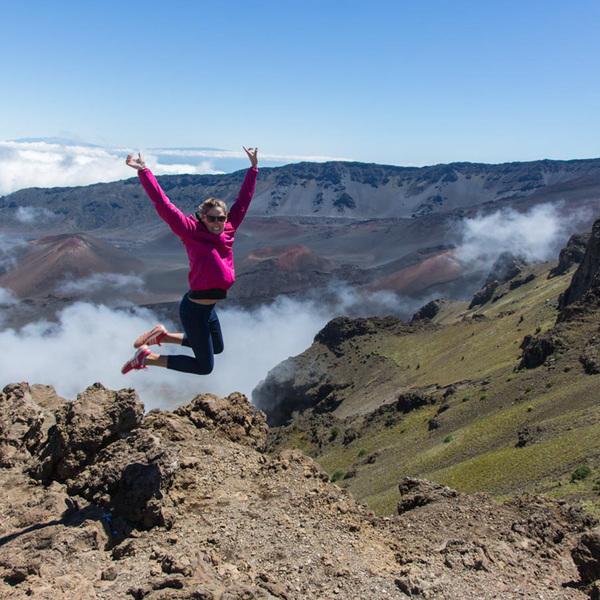 Une femme saute en l'air dans un paysage rocailleux entour de fumerolles