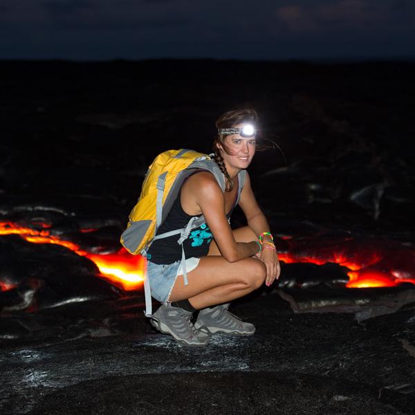 Une femme accroupie près d'une coulée de lave à la nuit tombée