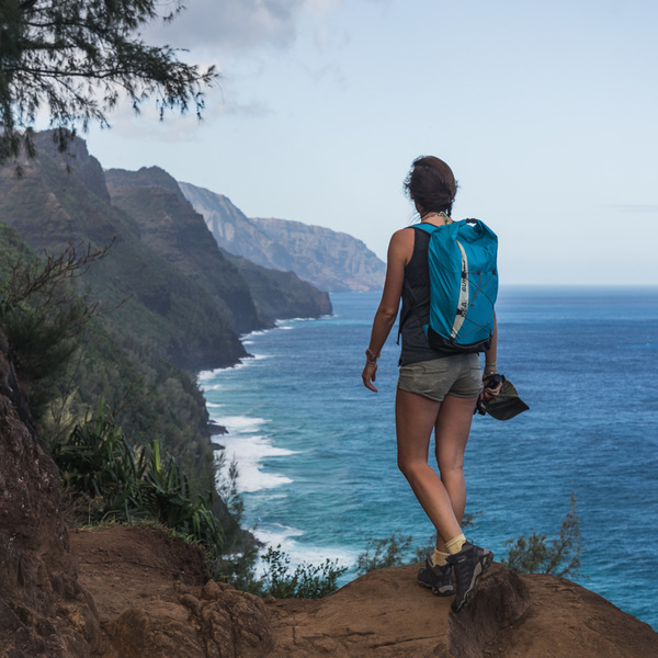 Une femme en train de randonner à flanc de falaise, face à l'océan Pacifique
