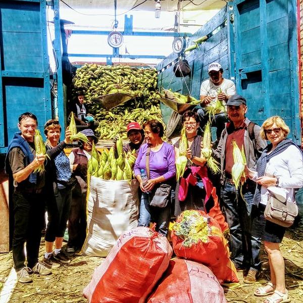 Groupe de voyageurs entourant des producteurs de maïs