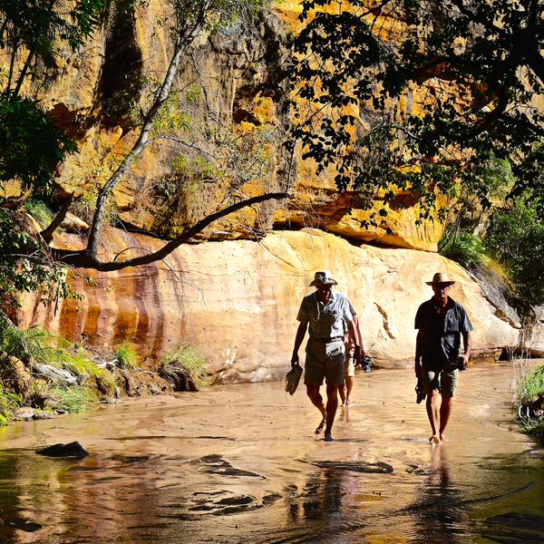 Deux marcheurs pieds nus dans l'eau au pied d'une falaise