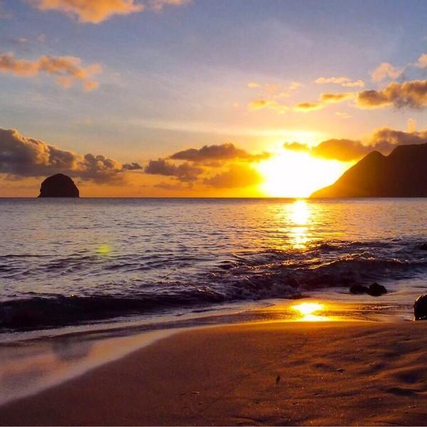 Coucher de soleil sur une plage avec la mer des Caraïbes et le relief des îles environnantes