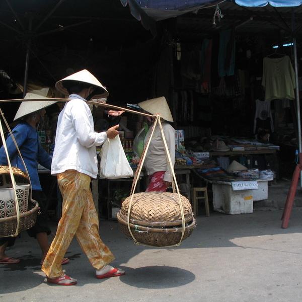 Tradizione e innovazione. Guarda cosa trasporta ! Un cesto tradizionale e una borsa in plastica, emblema dei contrasti del paese