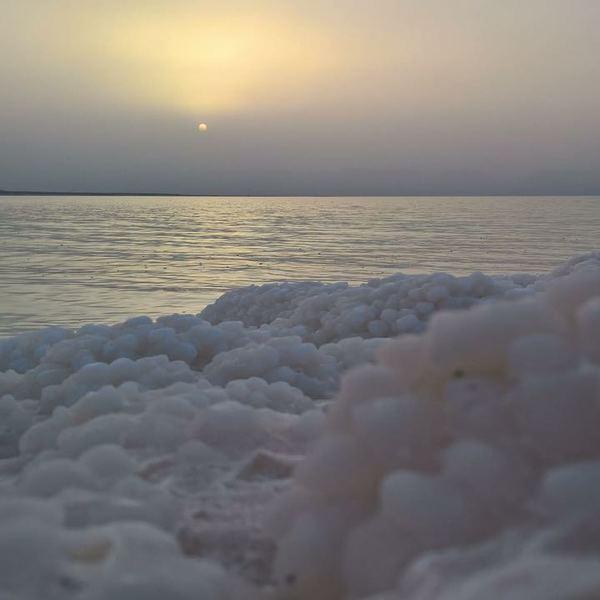 Croûtes de sel au bord de la Mer Morte et soleil voilé