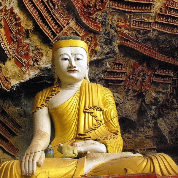 Une statue de bouddha tout de jaune vêtue devant la paroi ouvragée d'une grotte