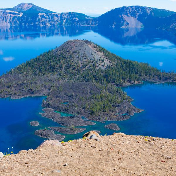 Ile en forme de cône volcanique au milieu d'un vaste lac cerclé d'une crête montagneuse