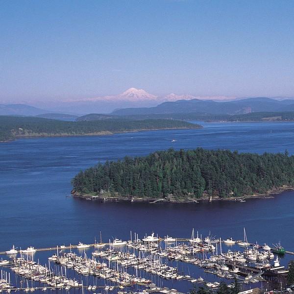 Chapelet d'îles sur une mer bleue avec un sommet enneigé qui émerge à l'horizon