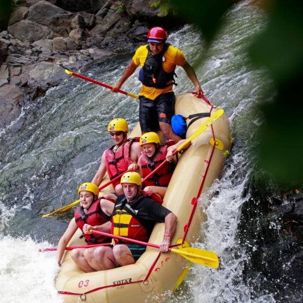 Das Bild zeigt ein Raftig-Boot, welches einen kleinen Wasserfall hinunter rutscht.