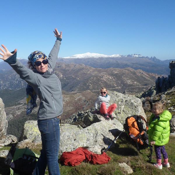 Une maman et ses enfants au sommet d'une montagne