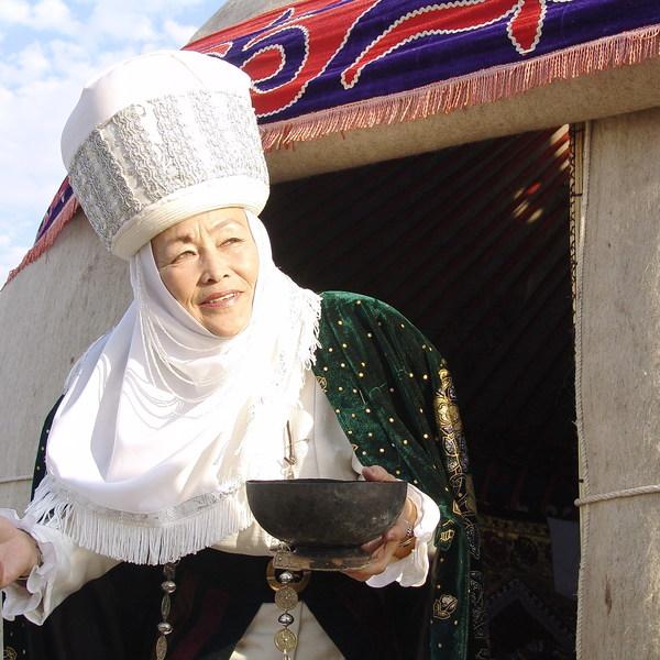 Une femme kirghize en costume traditionnel à l'entrée d'une yourte