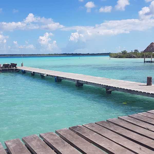Vue imprenable sur la lagune de Bacalar aux différents de bleus avec un ponton et des transats