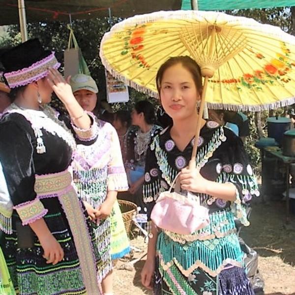 Femmes de l'ethnie Hmong en costume traditionnel, l'une d'elles se protégeant sous une ombrelle