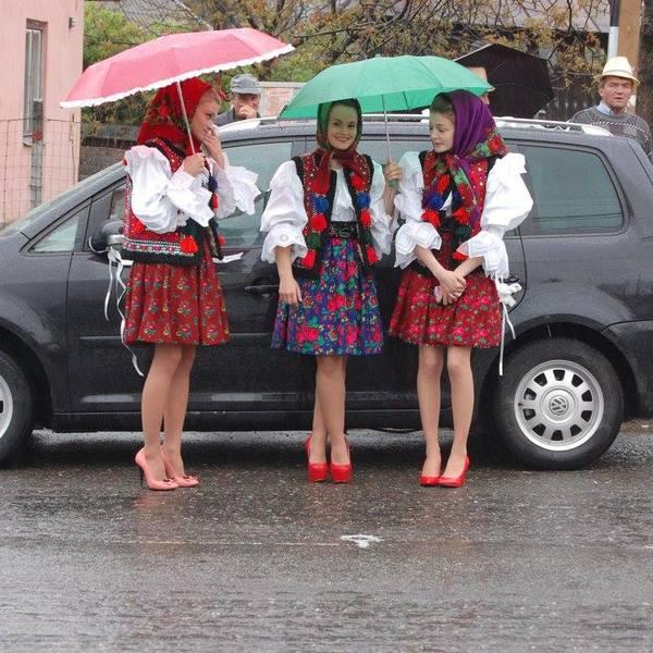Jeunes filles en tenues traditionnelles colorées se protégeant sous des parapluies
