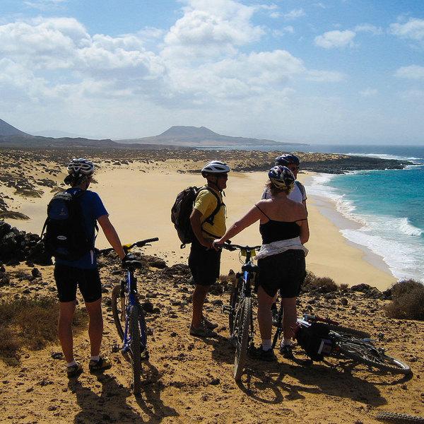 Groupe de cyclistes faisant une pause près d'une plage